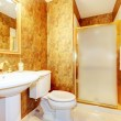 Golden antique bathroom with white toilet and sink. — Stock Photo