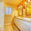 Bathroom with white cabinets and gold yellow walls. — Stock Photo