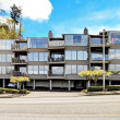 Apartment building with walkway with brenches. — Stock Photo