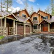 Stock Photo: Large mountain cabin house with stone and wet driveway.