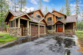 Large mountain cabin house with stone and wet driveway. — Stock Photo