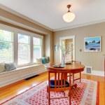 Elegant dining room with window bench with cherry hardwood floor. — Stock Photo
