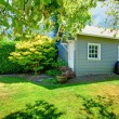 Small grey shed in the sunny green backyard. — Stock Photo