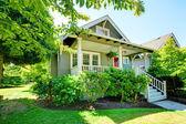 Pequeña casa gris con barandas de porche y blanco. — Foto de Stock