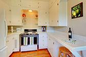 White kitchen with beige walls and cherry hardwood floor. — Stock Photo