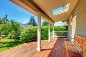 Large covered porch with skylight and wood bench and floor. — Stock Photo