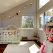 Baby girl room with white crib and clothes. — Stock Photo