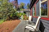 Wiosna podwórku dwa krzesła i czarny dom z drewna. — Zdjęcie stockowe