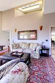Vardagsrum med högt i tak med röd matta och soffor. — Stockfoto