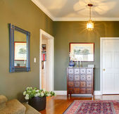 Classic Hallway with green walls, flowers and rug. — Stock Photo