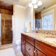 Large bathroom with cherry cabinets and granite countertop. - Stockfoto