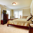 Large bright bedroom with wood furniture and beige tones. — Stock Photo