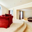 Large bright bedroom with red sofa and beige tones. — Stock Photo