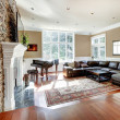 Bright luxury living room with stone fireplace and cherry hardwood. — Foto de Stock