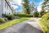 Home exterior of large grey classic house with long driveway. — Stock Photo