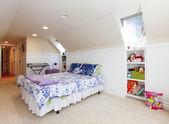 屋根裏部屋の天井とベージュのカーペットのおもちゃ女の子のベッドルーム. — ストック写真