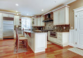Large white luxury kitchen with cherry hardwood. — Stok fotoğraf