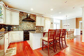 Luxury white kitchen with cherry hardwood and island with chairs. — Stock Photo
