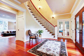 Luxury home entrance with cherry hardwood floor and staircase. — Stock Photo
