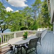 Stock Photo: Large long balcony home exterior with table and chairs, lake view.