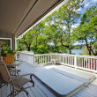 Large long balcony home exterior with hot tub and chairs, lake view. — Stock Photo #18287619