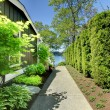 Side of the house with green landscape and walkway. - Stock Photo