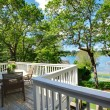 Large balcony home exterior with table and chairs, lake view. — Stock Photo