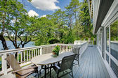 Large long balcony home exterior with table and chairs, lake view. — Stock Photo