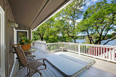 Large long balcony home exterior with hot tub and chairs, lake view. — Stock Photo