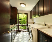 Laundry room with wood cabinets and white washer and dryer. — Stock Photo