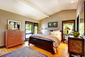 Chambre de luxe moderne avec lit, commode et table de chevet. — Photo