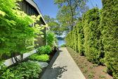 Po stronie domu z zielony krajobraz i chodnik. — Zdjęcie stockowe