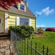 Yellow small classic home with water view and fence. - Stock Photo