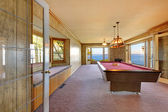 Large old room with pool table, window bench and water view. — Stock Photo