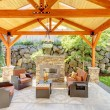 Exterior covered patio with fireplace and furniture. - Stock Photo