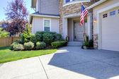 House exterior with driveway and American flag. — Stock Photo
