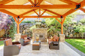 Exterior covered patio with fireplace and furniture. — Stock Photo