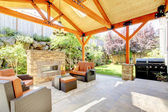 Exterior covered patio with fireplace and furniture. — Foto Stock