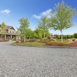 Large farm country house with gravel driveway and green landscape. — Stock Photo