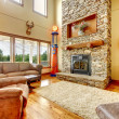 Living room with high ceiling, stone fireplace and leather sofa. — Stock Photo