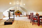 Velké dlouhé podkroví hry místnost s tv, bazén a sportovní zařízení. — Stock fotografie