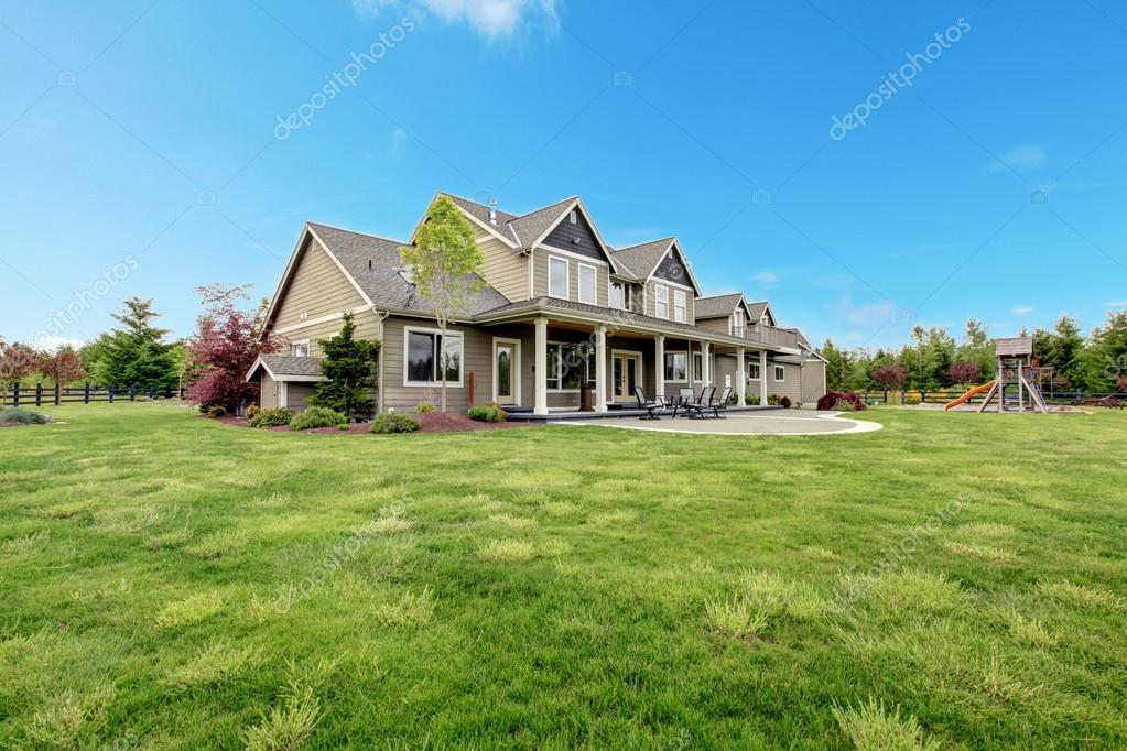 Large farm country house with spring green landscape, kids play ground.  Stock Photo #20330733