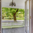 Open door to the front porch with view of the park. - Stock Photo