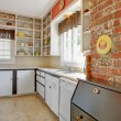 Old simple white kitchen with brick wall. - Stock Photo