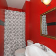Red small bathroom with white sink and shower. - Stock Photo