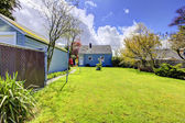 Backyard with small blue house and bright green spring grass. — Stock Photo
