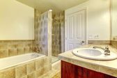 Bathroom with tub, small shower and wood cabinets. — Stock Photo