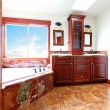 Luxury new home bathroom with red marble and mahogany wood. — ストック写真