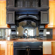 Kitchen island and stove custom wood cabinets. New luxury home interior. — Foto de Stock