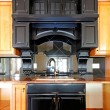 Kitchen island and stove custom wood cabinets. New luxury home interior. - Stock Photo